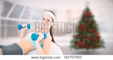 Smiling fit woman exercising with dumbbells on fitness ball against home with christmas tree