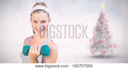 Sporty happy blonde lifting dumbbell on the beach against blurry christmas tree in room