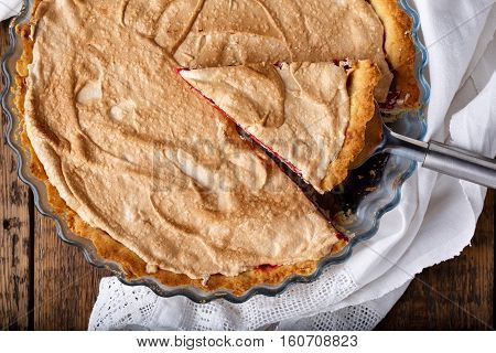 Homemade cowberry tart with merengue. Rustic style. Top view.