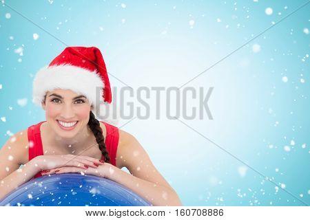 Festive fit brunette leaning on exercise ball against christmas snow falling