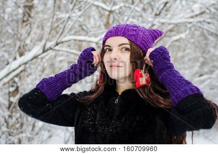 Long-haired brunette girl walking in a winter forest with red felt hearts in her hands