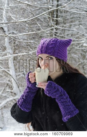 Long-haired brunette girl walking in a winter park and drinking coffee with marshmallow wearing a black fir coat a handmade purple cat hat and gloves