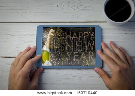 Hands using tablet on desk against composite image of champagne bottle with ice cube