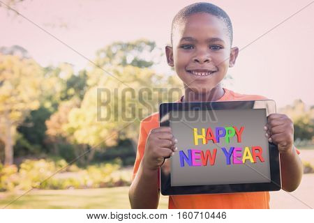 New year greeting against portrait of boy smiling while holding digital tablet