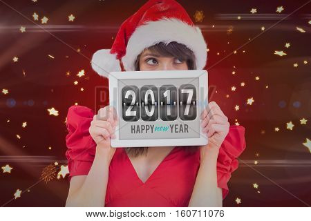 Digital composite of Pretty girl showing tablet with 2017 on it
