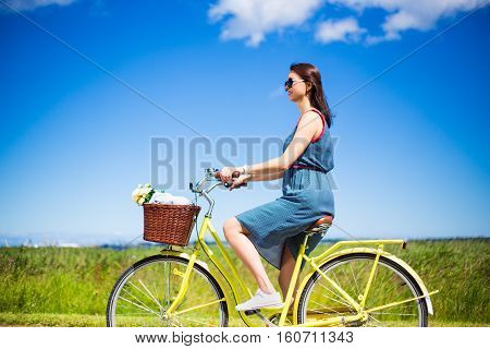 Side View Of Beautiful Woman Riding Vintage Bicycle In Countryside