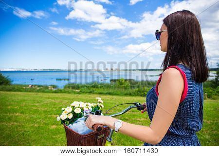 Back View Of Woman With Vintage Bicycle And Flowers In Wicker Basket On The Beach