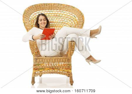 View of very happy woman smiling with tablet over wicker chair