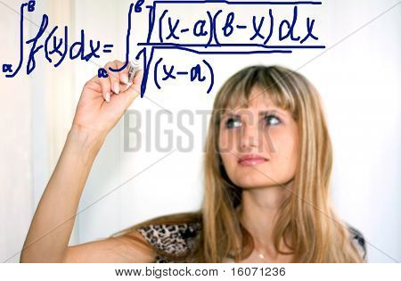 girl writing math formulas on a white-board