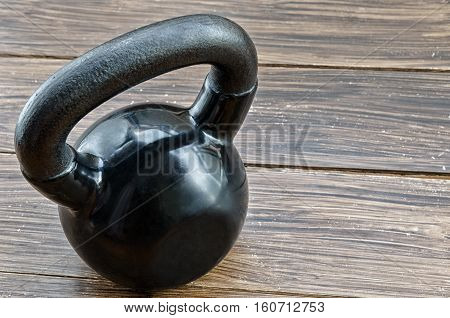 Black kettlebell on wooden background with copyspace. Concept for sport and gym.