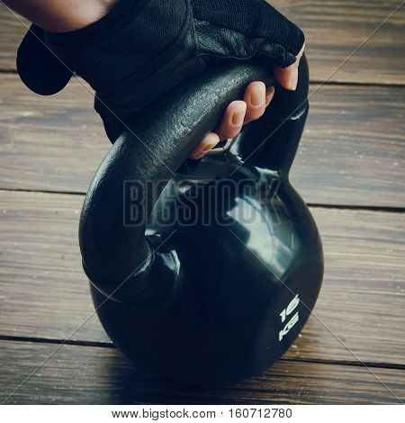 Close up of black kettlebell and sport gloves on dark background. Concept for gym and fitness.