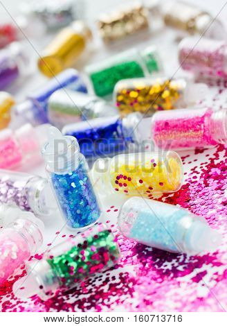 Transparent small bottles with glitter makeup and nail art selective focus