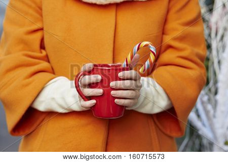 Woman Hands In Woolen Mittens With Mug And Christmas Candy Cane