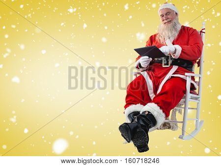 Santa sitting on chair and using digital tablet against yellow background