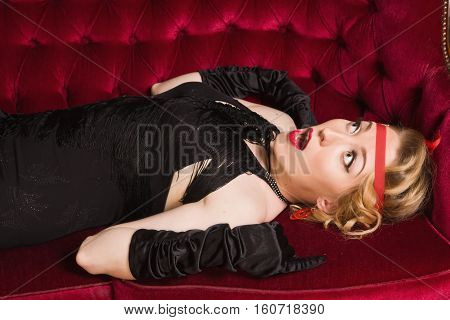 Elegant Frightened Woman In Retro Style Lying On A Sofa.