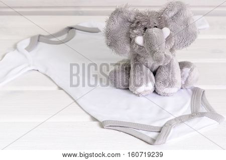 Baby Bodysuit And Soft Toy On White Wooden Background