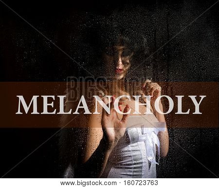 melancholy written on virtual screen. hand of young woman melancholy and sad at the window in the rain