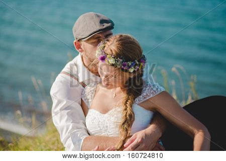 HAMBURG, GERMANY - June 01, 2016: Bride and groom sitting in a field in an embrace overlooking the seaside.