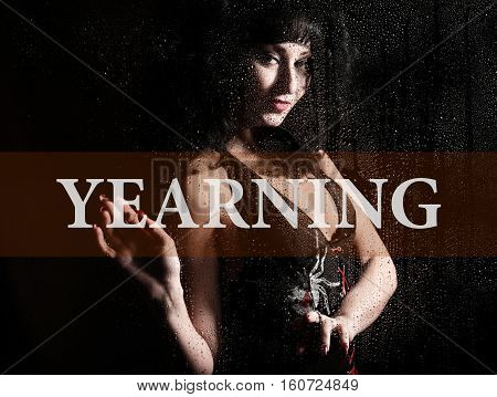 yearing written on virtual screen. hand of young woman melancholy and sad at the window in the rain