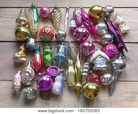 Many vintage glass Christmas toys on a wooden surface.