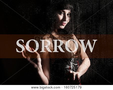 sorrow written on virtual screen. hand of young woman melancholy and sad at the window in the rain