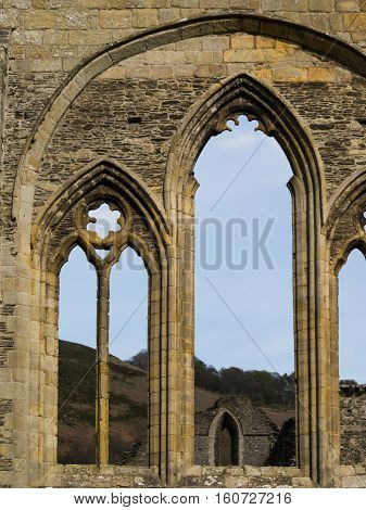 Detail from the evocative ruins of Valle Crucis Abbey which lies in green fields beneath Llangollen's steep sided mountains.