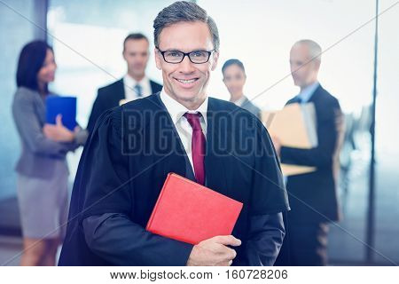 Portrait of lawyer holding law book in office