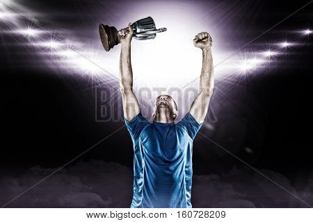 Happy rugby player holding trophy against spotlight 3D