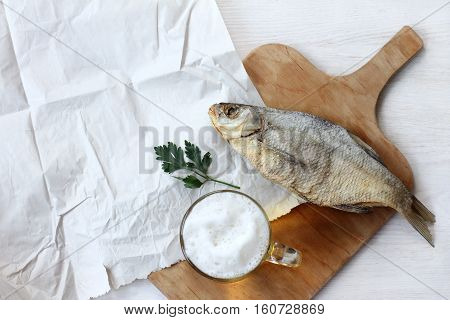 foamy beer in transparent mug and salted fish top view / still life with drinks and snacks