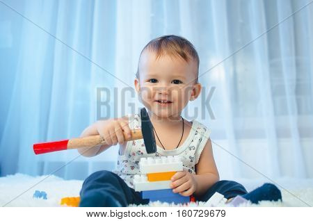 The child is sitting on the bed with a hammer and bet the designer