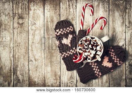 Winter Love or Christmas Concept with Gloves Candy Canes and Hot Chocolate on a Wooden Background. Top View View from Above with Copy Space