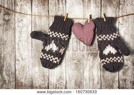 Winter Love or Valentine's Day Concept with Gloves and Red Plush Heart on a Wooden Background. Top View View from Above with Copy Space