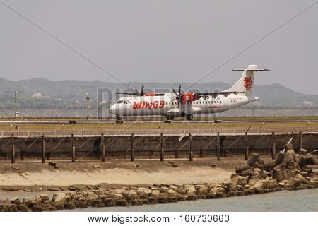 BALI - April 3 2016: Wings Abadi Airlines or Wings Air is a low cost airline and a schedule commuter passenger airline based in Jakarta Indonesia. Plane lands on the runway at the airport in Bali.