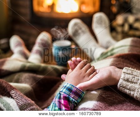 Warming and relaxing near fireplace. Mother and daughter holding hands in front of fire.