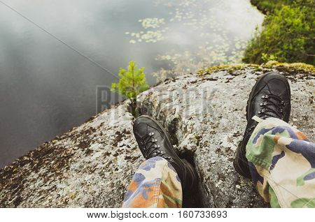 Male Feet In Camouflage Pants Near Lake