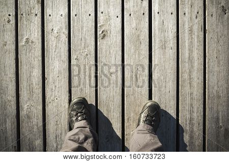 Male Feet Stand On Old Wooden Pier