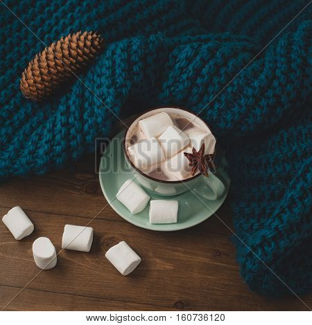 winter home background - cup of hot cocoa with marshmallow and blue knitted sweater and book on wooden table.