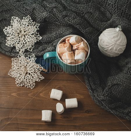 cozy winter home background - cup of hot cocoa with marshmallow Christmas ball snowflakes and warm gray knitted sweater book on wooden table.