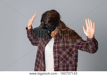 portrait of charming woman testing virtual reality glasses in studio on grey background