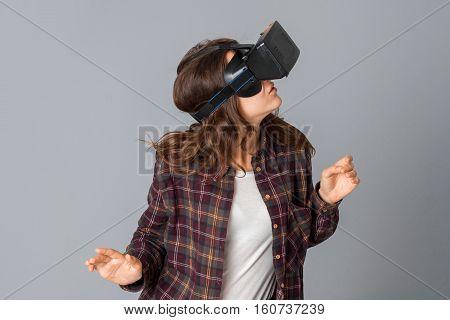 portrait of woman testing virtual reality helmet in studio on grey background