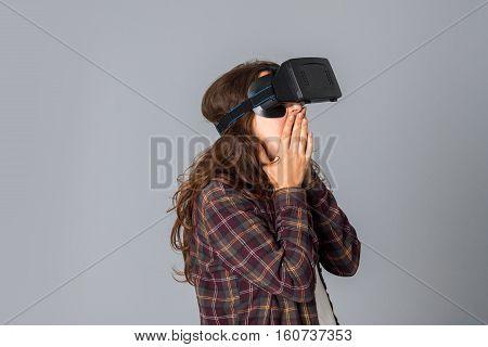 portrait of funny woman testing virtual reality helmet in studio on grey background