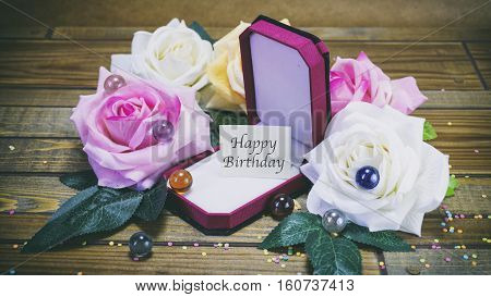 Honeymoon Gift Box And Flowers On Wooden Background, A Note On The Paper