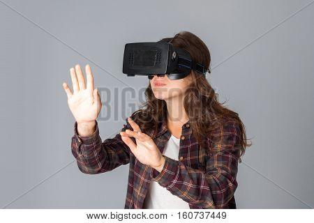 portrait of beautiful woman testing virtual reality helmet in studio on grey background