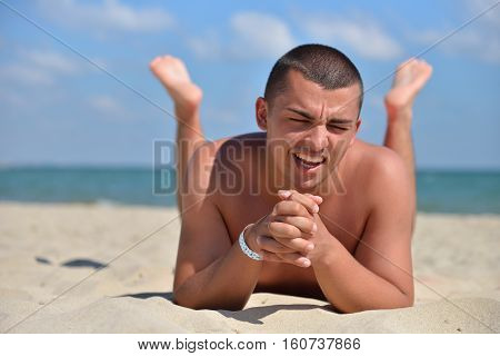 Happy Man On Beach Lying In Sand Looking At The Camera. Young Male Enjoying Summer Travel Holiday Re