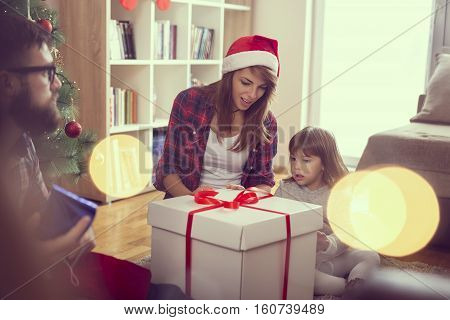 Young family enjoying Christmas morning together exchanging presents and having fun