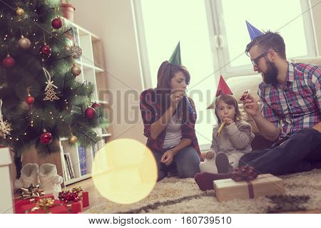 Beautiful young family sitting next to a nicely decorated Christmas tree wearing Santa's hats and blowing party whistles. Focus on the father