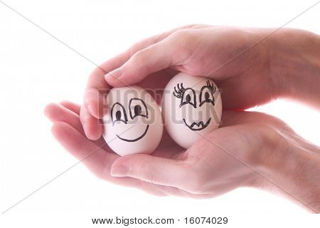 Two eggs in hands isolated on white