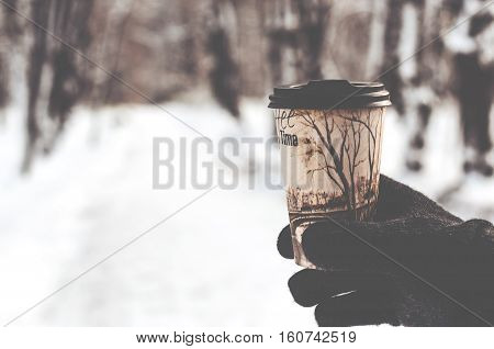 glass with hot coffee in male hand outdoors in winter
