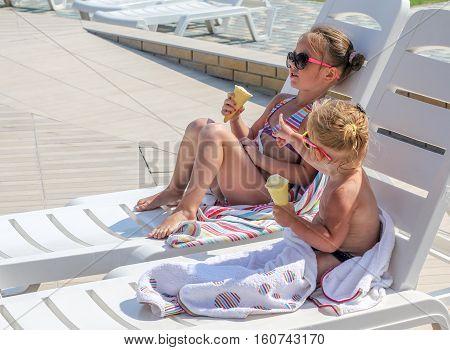 Baby Girl Eating Ice Cream Near The Pool