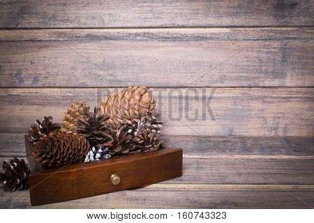 Christmas still life with cones in a wooden box on the wooden background. Copy space